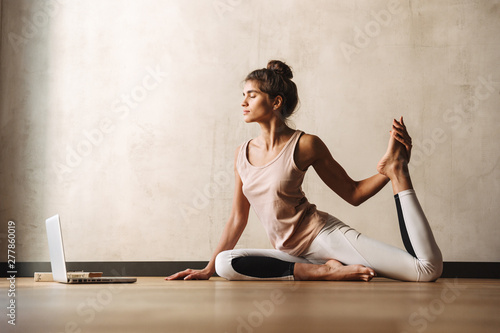 Obraz Photo of young concentrated woman doing yoga exercises using laptop while sitting on floor at home - fototapety do salonu
