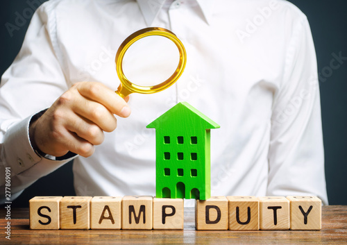 Businessman and wooden blocks with the word Stamp duty and house Fotobehang