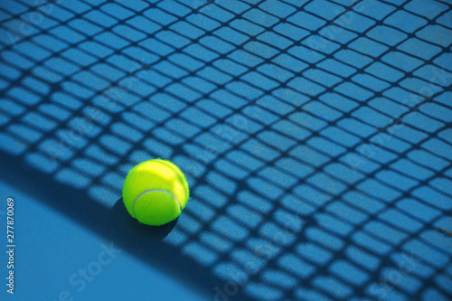 Summer sport concept with tennis ball and net on hard tennis court. Flat lay, top view, copy space.