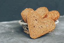 Rye Bread In The Shape Of Heart Cut Into Slices On A Gray Background