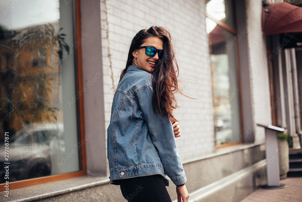 Fototapeta Happy attractive young woman in sunglasses walking in the city. Playful woman wraps herself over her shoulder and looking in camera.