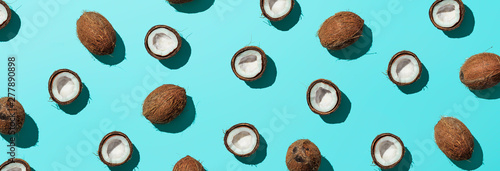 Creative layout of coconuts half on blue background. Tropical pattern, top view or flat lay. Hard light pop art minimal summer background. Horizontal banner