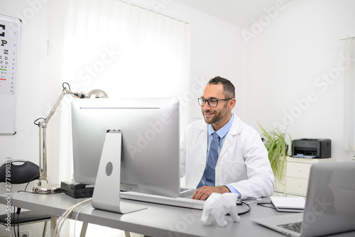 Fototapeta portrait of a handsome man male doctor in medical practice office working on computer obraz