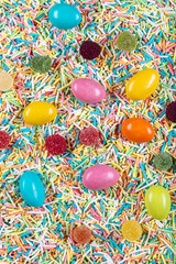 Fototapeta na wymiar variety of candies on a wooden background with space for text. Colorful sugar sprinkles. Easter