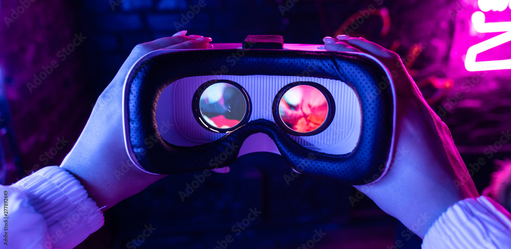 Fototapeta Female hands hold 3d 360 vr headset wear ar innovative glasses goggles on camera in futuristic purple neon light, girl gamer virtual augmented reality technology background concept, close up view