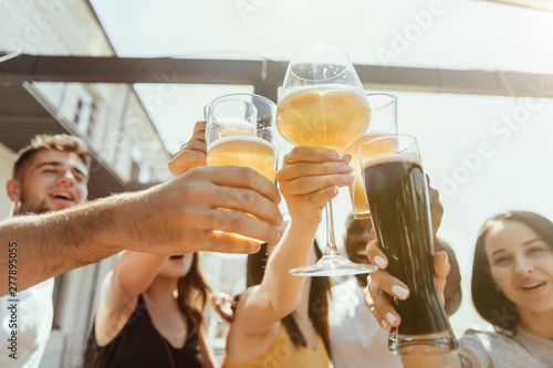 Платно Young group of friends drinking beer, having fun, laughting and celebrating together