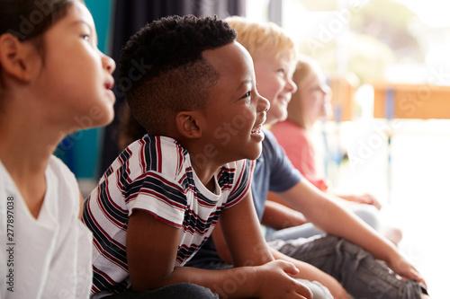 Obraz Group Of Elementary School Pupils Sitting On Floor Listening To Teacher - fototapety do salonu