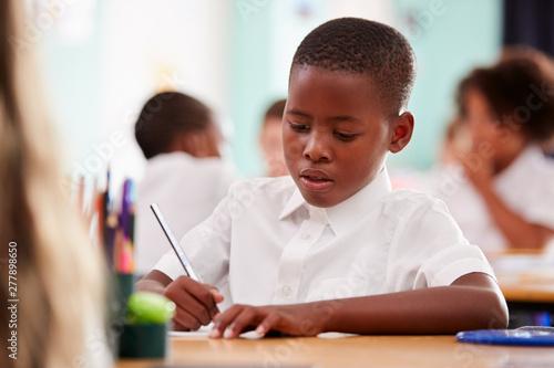 Male Elementary School Pupil Wearing Uniform Working At Desk Fototapeta