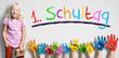 """Leinwandbild Motiv viele angemalte Kinderhände mit Smileys vor Wand mit dem Wort """"1. Schultag"""""""