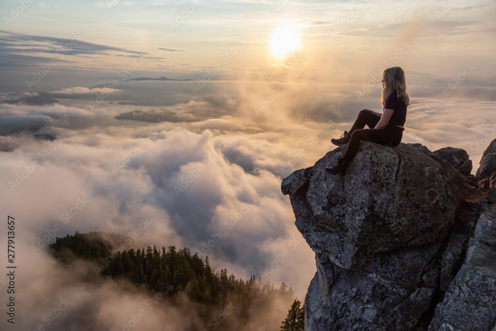 Fototapeta Adventurous Female Hiker on top of a mountain covered in clouds during a vibrant summer sunset. Taken on top of St Mark's Summit, West Vancouver, British Columbia, Canada.