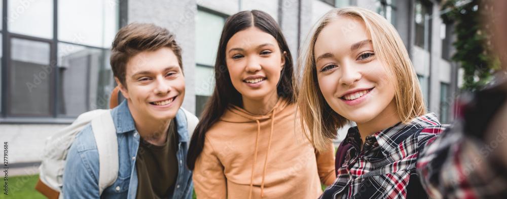 Fototapeta panoramic shot of happy teenagers taking selfie and smiling