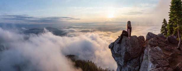 Avanturistički planinar na vrhu planine prekrivene oblacima za vrijeme živahnog ljetnog zalaska sunca. Snimljeno na vrhu summita Svetog Marka, zapadni Vancouver, Britanska Kolumbija, Kanada.