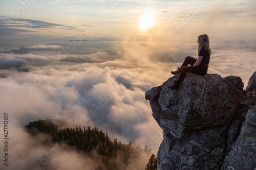 Obraz na plátně  Adventurous Female Hiker on top of a mountain covered in clouds during a vibrant summer sunset