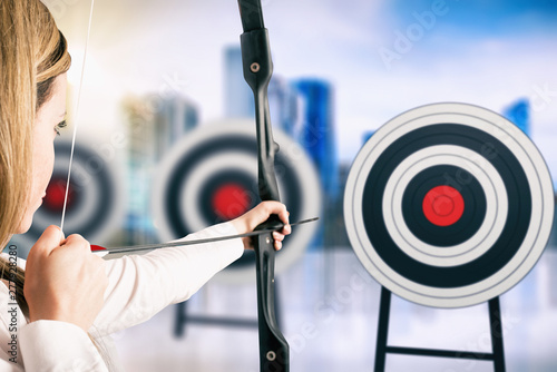Photo  Businesswoman with bow and arrow pointing the center of the target