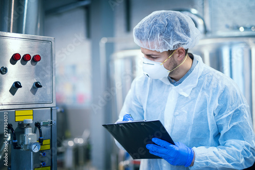 Fotografía  Technologist expert in protective uniform with hairnet and mask taking parameters from industrial machine in food production plant