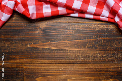 a checked gingham picnic tablecloth on old wooden table top view Fototapeta