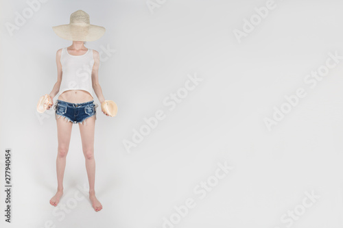 Fotografering  the girl in shorts and hat covering her face staying and holding the clamshells