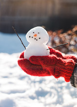 Close Up Of Hands In Red Wool Mittens Holding A Small Snowman.