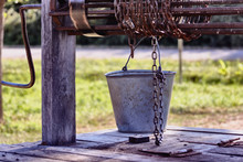 Old Wooden Well With A Rusty Collar, Drum, Chain And Bucket.
