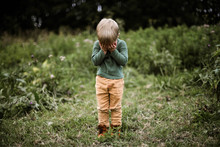 Little Adorable Boy Covers His Eyes With His Hands Standing Outdoor