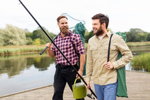 Leisure And People Concept - Male Friends With Net And Fishing Rods On Lake Pier