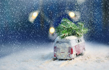 Christmas Card With Little Vintage Bus With Christmas Tree On The Roof. Car Sneaks Through The Snowfall. Christmas Background.