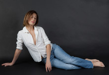 Seated Woman In Jeans And Whit...