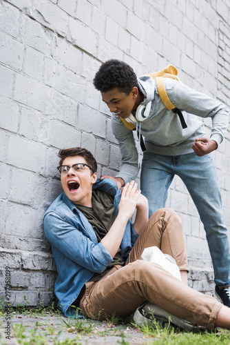 Valokuva aggressive and brunette african american boy going to punch frightened boy in gl