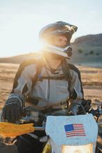 Man Sitting On Motorbike In Desert