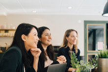 Smiling Businesswomen Sitting In Conference Room