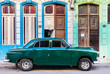 Green vintage car parked in front of house entrances, Havana, Cuba