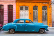 Parked blue vintage car in front of residential house, Havana, Cuba