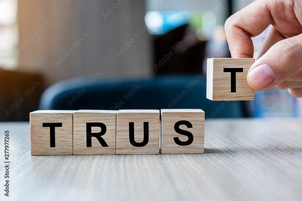 Fototapeta Businessman hand holding wooden cube block with TRUST business word on table background. Trustworthy, Truth, beliefs and agreement concept