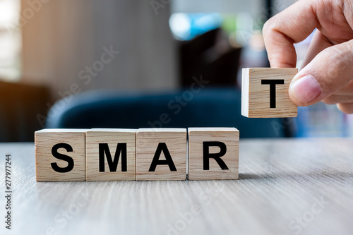 Fotografía Businessman hand holding wooden cube block with SMART business word on table background