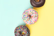 Three tasty doughnuts on turquoise background.