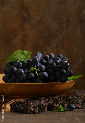 black ripe organic grapes on a wooden table, rustic style Fototapete