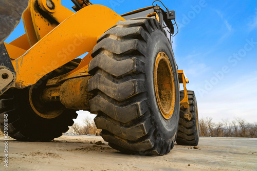 Fotografiet  Close up view of the huge black rubber tires of a yellow construction vehicle
