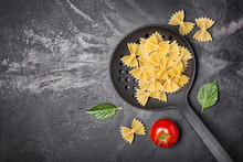 Raw Farfalle Pasta In Black Skimmer With Basil And Cherry Tomatoes