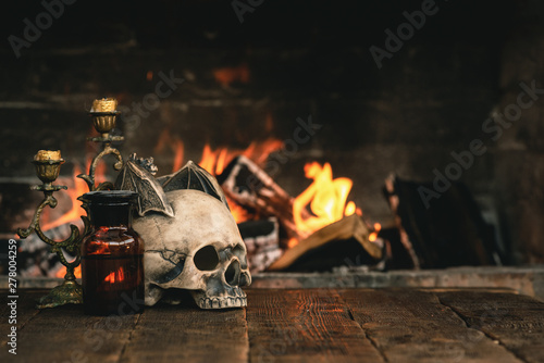 Fototapeta  Alchemist or wizard or witch doctor table with magic accessories above on a burning fire background