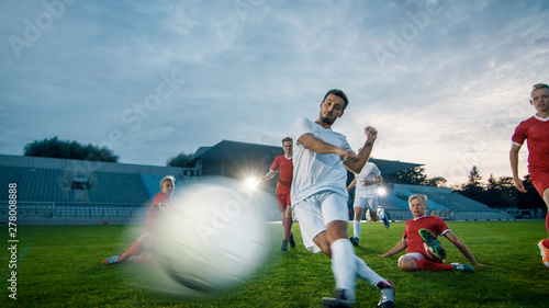 Fotografie, Tablou  Professional Soccer Player Outruns Members of Opposing Team and Kicks Ball to Score Goal