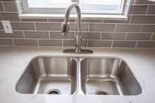 Double Bowl Stainless Steel Sink Undermounted On The White Kitchen Countertop