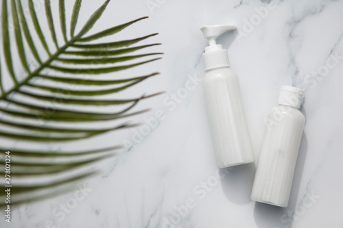 Fototapeta Skincare and cosmetic products on a marble background with tropical palm leaf obraz na płótnie