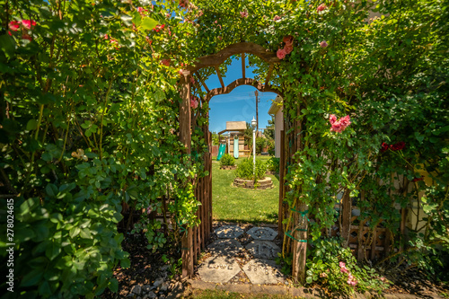 Canvastavla Arched wooden arbor at the entrance of a garden with playhouse slides and swings