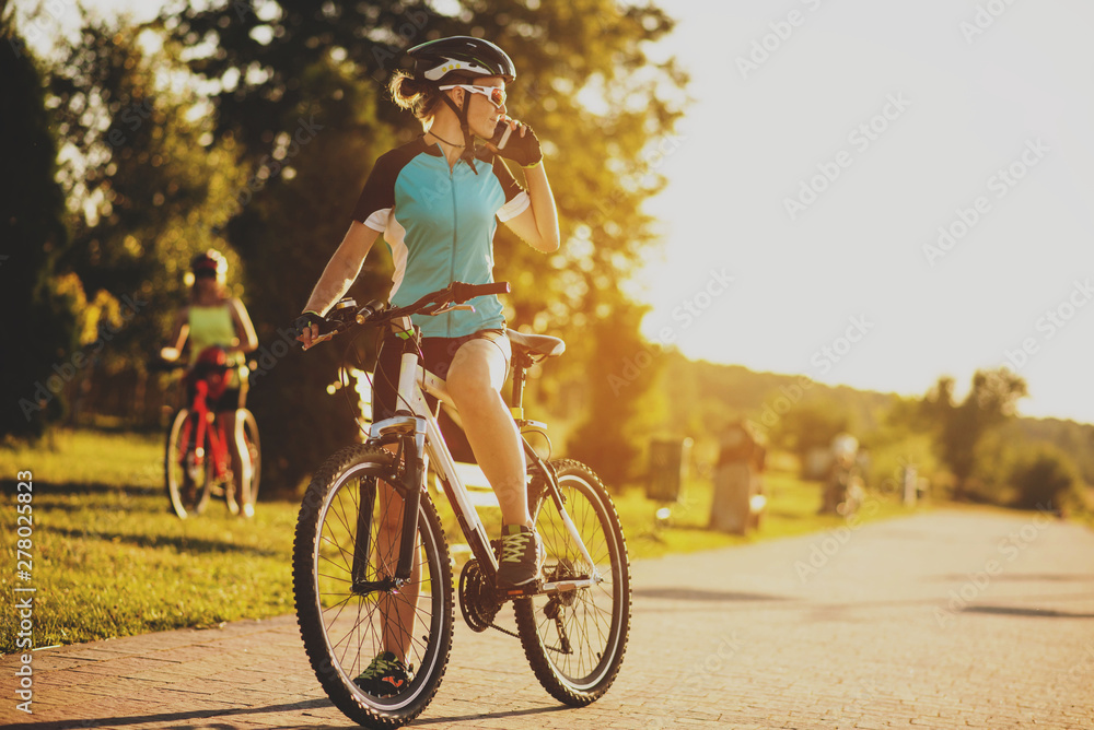 Fototapeta Two women friends riding on bikes at the sunset