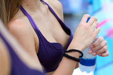 Hands Of A Girl In Bikini Holding A Bottle With Mineral Water