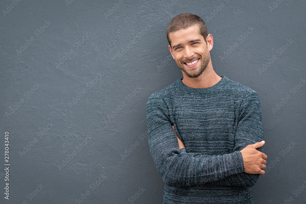 Fototapeta Smiling young man leaning against grey wall