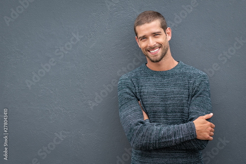 Smiling young man leaning against grey wall