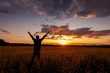 Silhouette of a man raise his hands up to sunset on the field with wheat or rye.