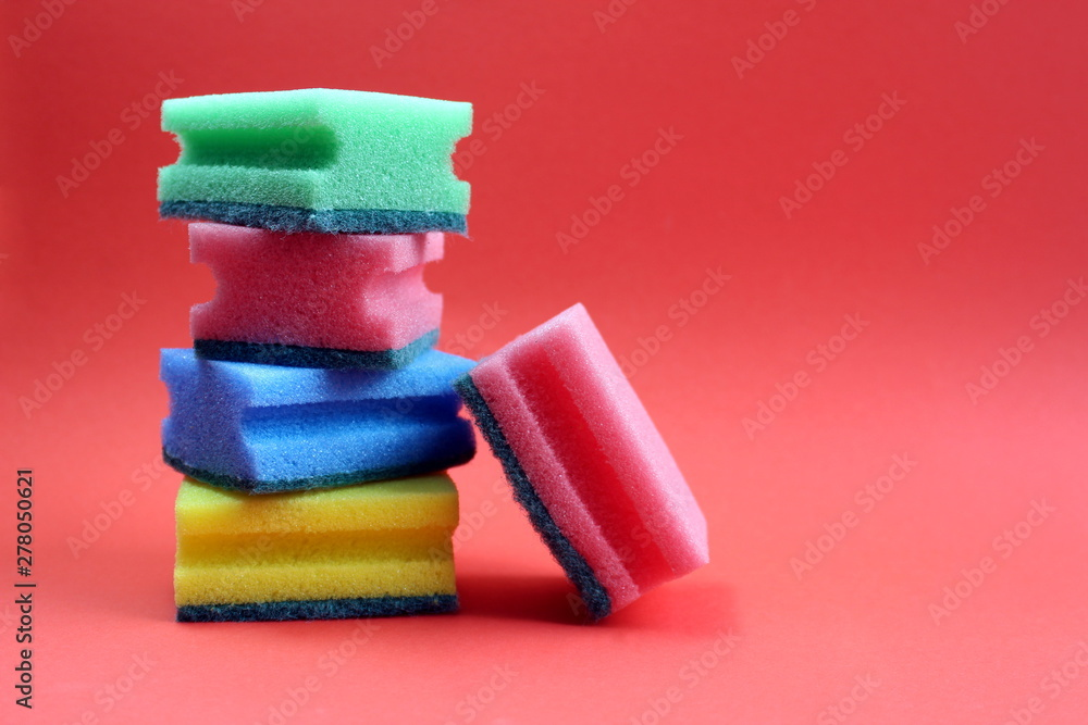 Fototapeta Folded scouring sponges in a single stack on a red background.