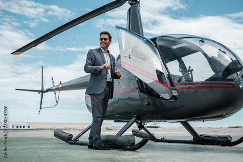 Photo Businessman standing near private helicopter